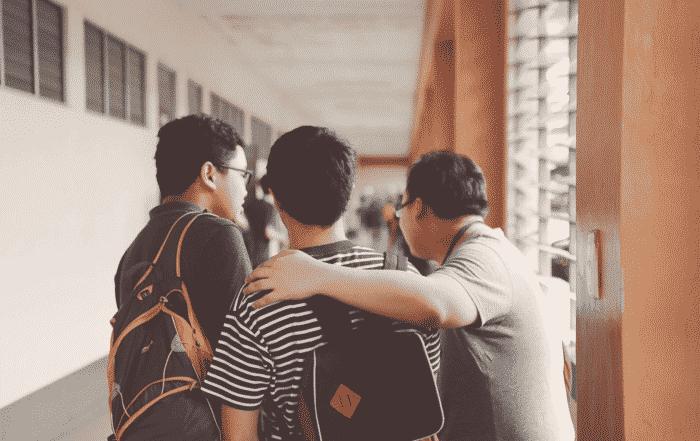 three students standing near the door