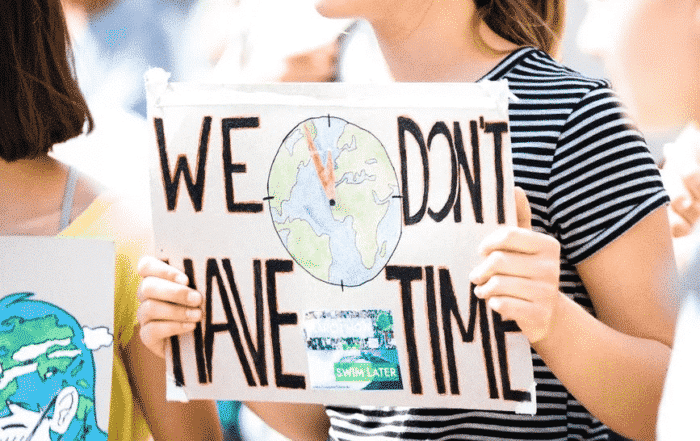 "student holding a sign ""we don't have time"""