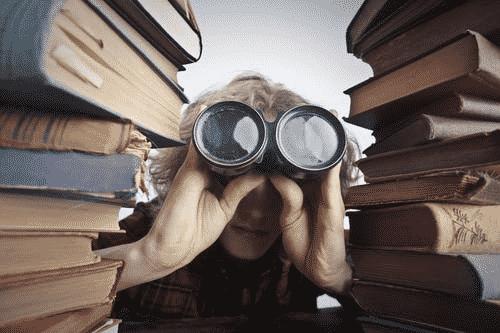Boy with binoculars in between stacks of books