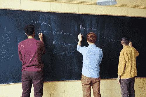 Three young boys writing on a chalkboard